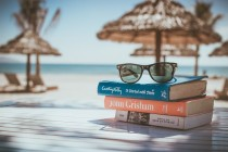 Picture of a pair of glasses on top of a pile of books. Background is a beach with umbrellas